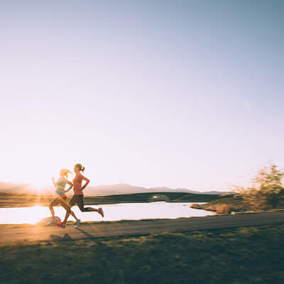 two women wearing performance cotton activewear run at sunrise by a lake