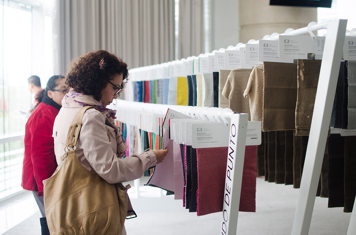 woman with purse looking at fabric sample