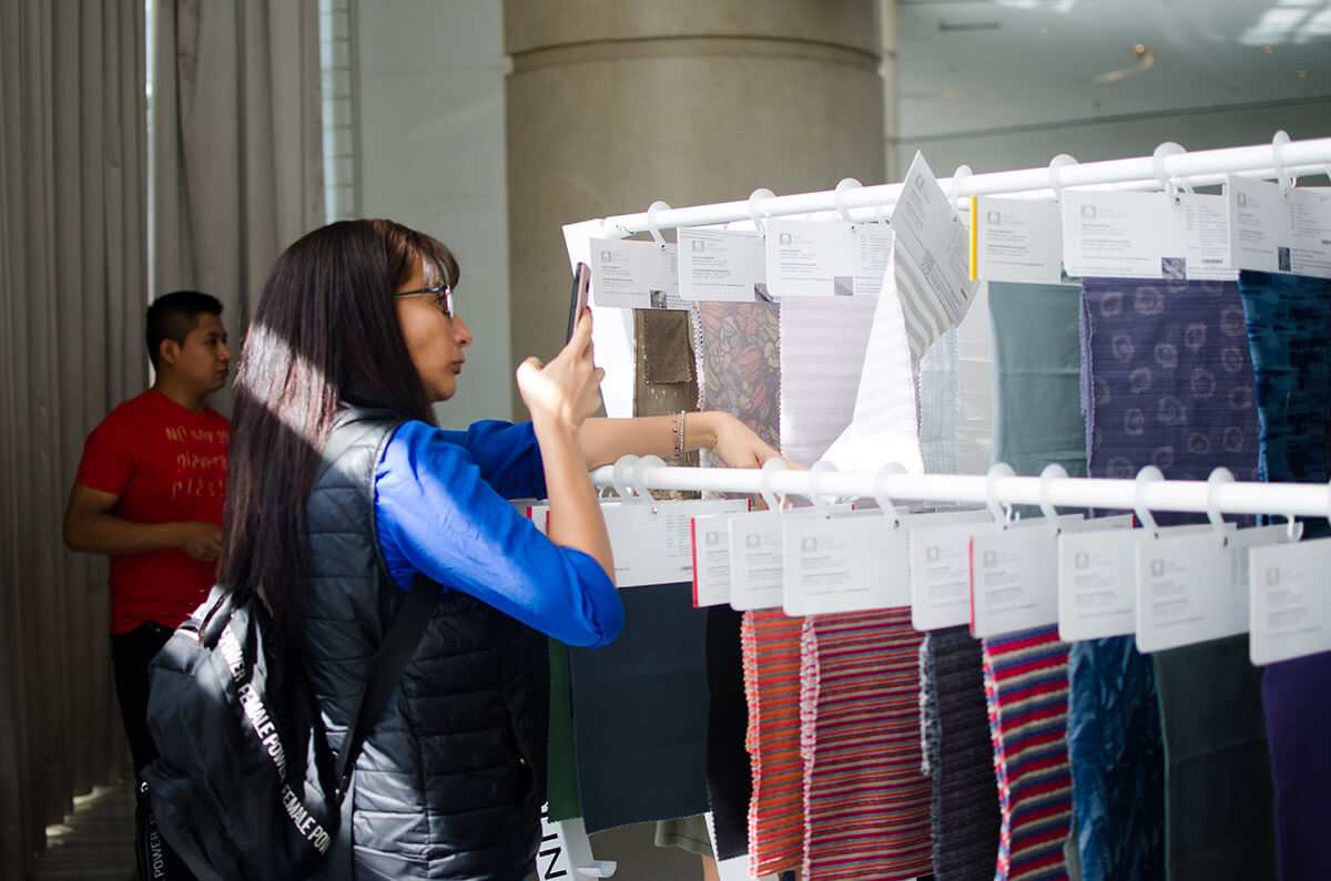 woman looking at fabric samples taking photo with phone