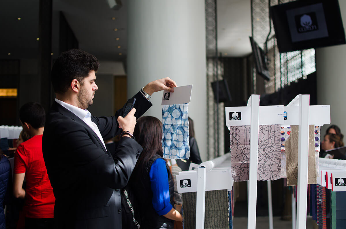 man in suit looking at fabric sample taking photo with phone