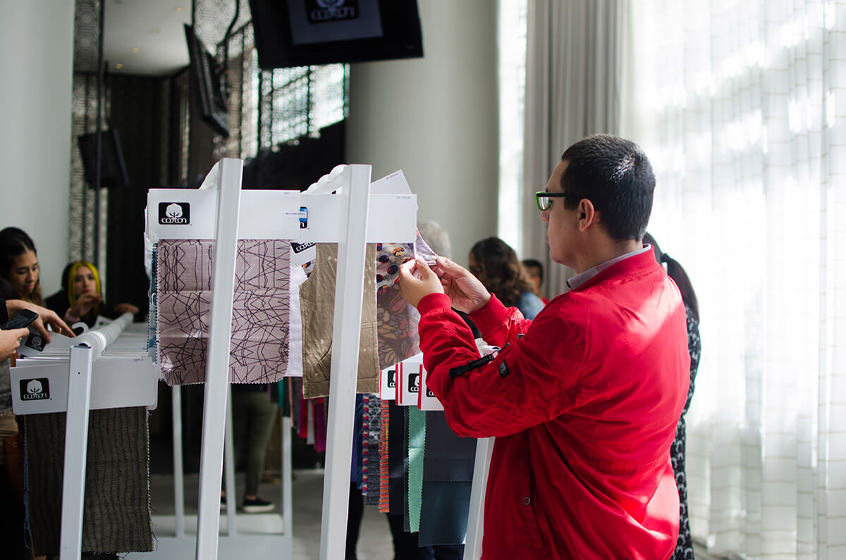man in red looking at fabric samples